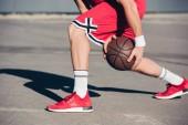 cropped image of basketball player playing basketball on street