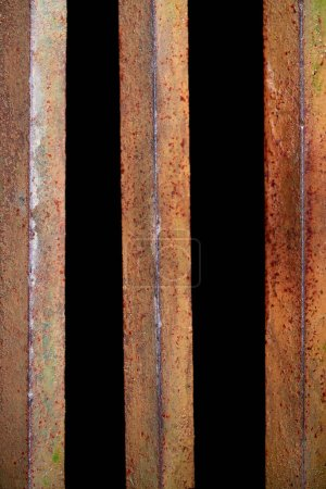 close up view of rust fence with black background behind