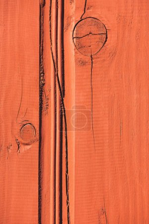 close up of orange wooden fence with cracks