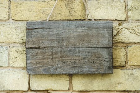 empty wooden board hanging on brick wall
