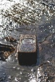 water dripping on brick in river, sun reflecting on surface
