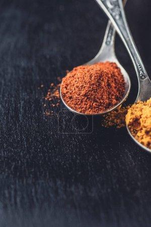 vue rapprochée des cuillères avec piment en poudre et de curry sur fond noir