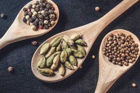 vue rapprochée des cuillères en bois avec des grains de poivre, graines de coriandre et cardamome sur fond noir
