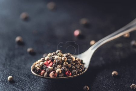 close-up view of spoon with dried aromatic peppercorns on black