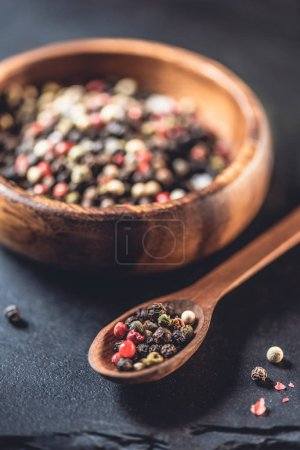 close-p view of wooden spoon and bowl with dried aromatic peppercorns on black