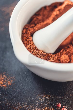 close-up view of white bowl with aromatic dried chili powder on black