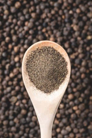 close-up view of wooden spoon with powdered pepper and peppercorns