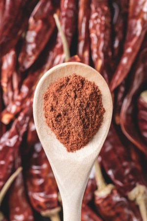 close-up view of wooden spoon with chili powder above red hot chili peppers