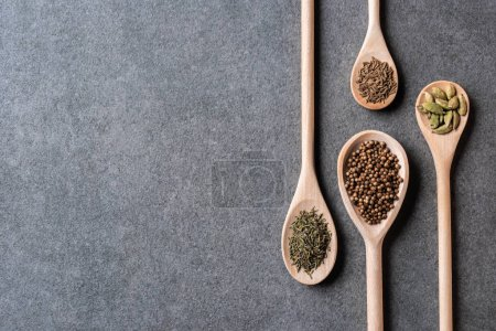 top view of wooden spoons with dried aromatic seasonings on grey background