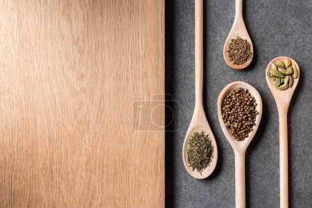 top view of dried spices on wooden spoons and wooden board on grey background
