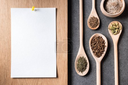 top view of dried spices on wooden spoons and blank paper sheet