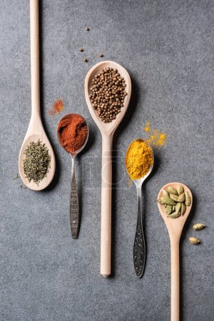 top view of different dried aromatic spices in spoons on grey  background