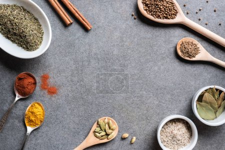 various aromatic dried seasonings in bowls and spoons on grey background