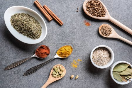 top view of various aromatic dried seasonings in bowls and spoons on grey surface