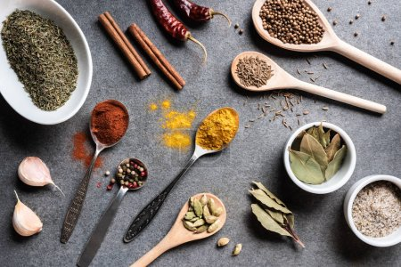 top view of various aromatic dried spices in bowls and spoons on grey surface