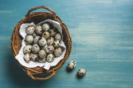 top view of raw healthy quail eggs in wicker basket on turquoise wooden table