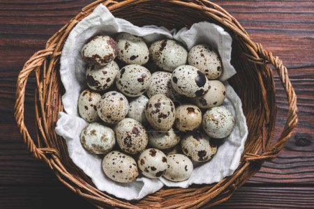 top view of raw healthy quail eggs in wicker basket on wooden table
