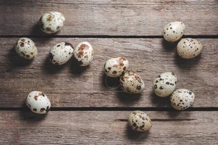 top view of fresh raw healthy quail eggs on rustic wooden table