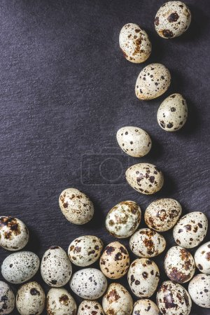 top view of organic unshelled quail eggs on black background