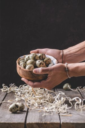 cropped shot of person holding bowl with quail eggs above wooden table with shavings