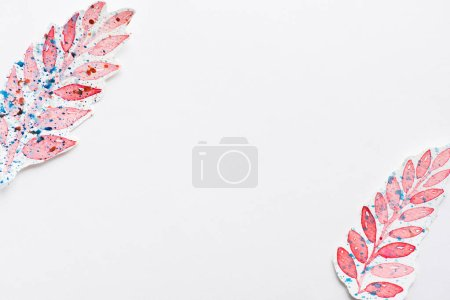 Top view of paintings of leaves made by pink with splashes of blue paints on white background