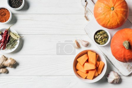 Photo for Top view of spices, pumpkins, garlic and cutting board on table - Royalty Free Image
