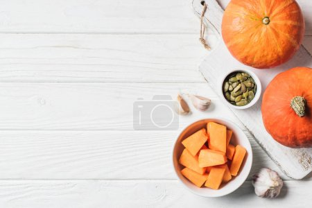 elevated view of pumpkin pieces in bowl, pumpkin seeds and garlic on table
