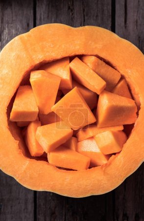 elevated view of raw pumpkin with pieces inside on wooden table