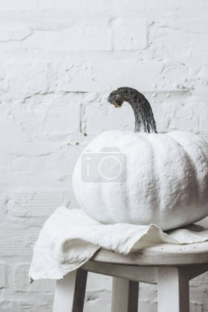 close-up shot of halloween pumpkin painted white in front of white brick wall