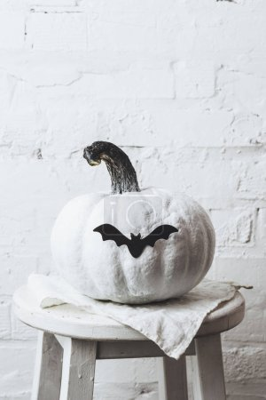 close-up shot of white painted halloween pumpkin with bat sticker in front of white brick wall