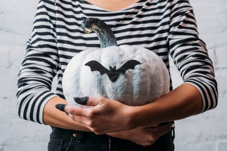 cropped shot of woman holding white painted halloween pumpkin with bat sticker
