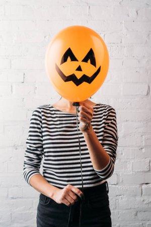 Photo pour Femme tenant ballon halloween devant la tête - image libre de droit
