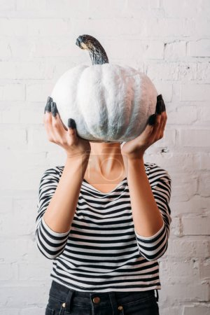 woman in striped shirt holding white painted halloween pumpkin in front of head