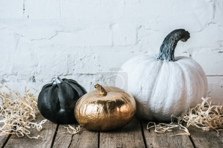 still life of various painted halloween pumpkins on wooden surface