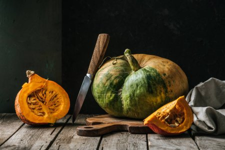 Photo for Close up view of food composition with pumpkins, knife and cutting board on wooden surface on dark background - Royalty Free Image