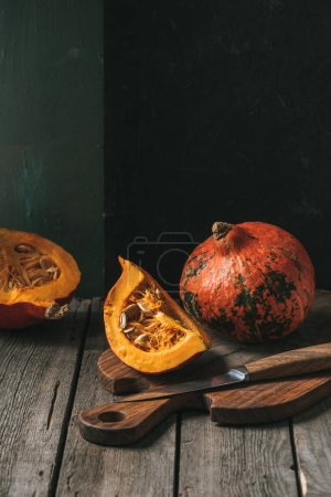close up view of raw cut pumpkins arranged on cutting board with knife on dark backdrop