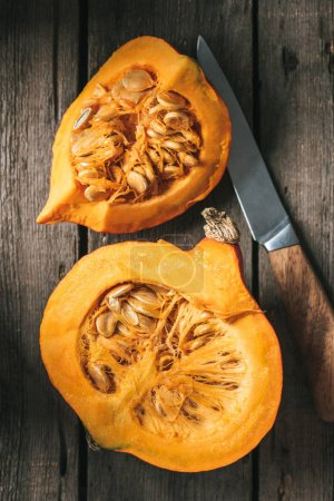 Photo for Flat lay with knife and raw pumpkin halves on wooden background - Royalty Free Image