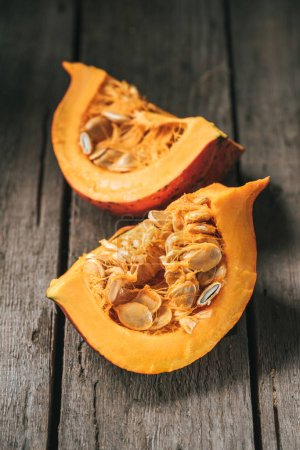 Photo for Close up view of raw pumpkin halves on wooden background - Royalty Free Image