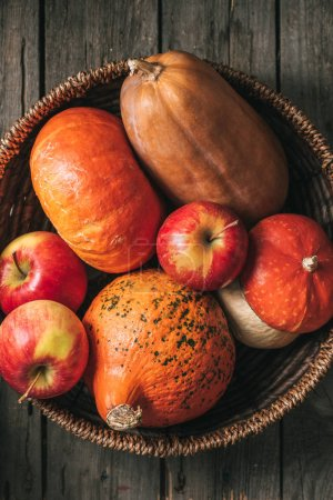 Top view of ripe apples and pumpkins autumn harvest in basket on  wood background