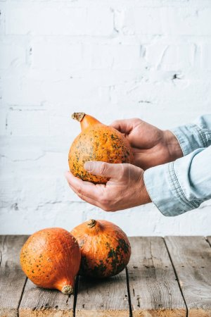 partial view of man and ripe pumpkins on wooden tabletop and white brick wall backdrop