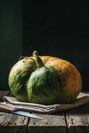 close up view of raw pumpkin on linen and knife on black background