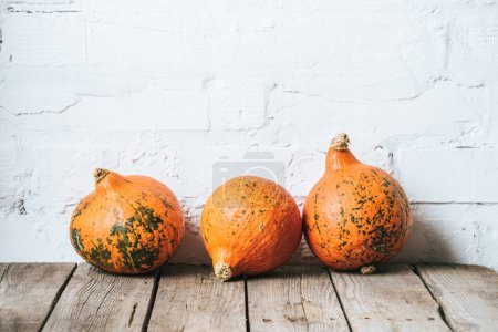 close up view of arranged ripe pumpkins on wooden tabletop and white brick wall backdrop