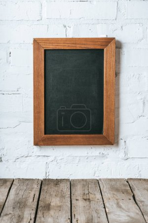 close up view of blank chalkboard on white brick wall and wooden planks surface