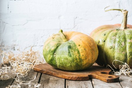 close up view of ripe pumpkins on cutting board on wooden surface and white brick wall background