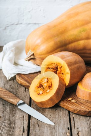 close up view of cut pumpkins on wooden tabletop and white brick wall background