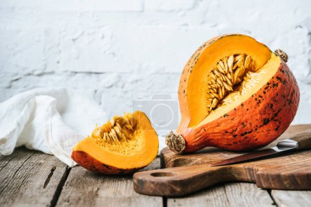 close up view of cut pumpkin on cutting board on wooden surface and white brick wall background