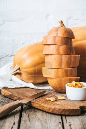close up view of arranged pumpkins and knife on wooden surface and white brick wall background