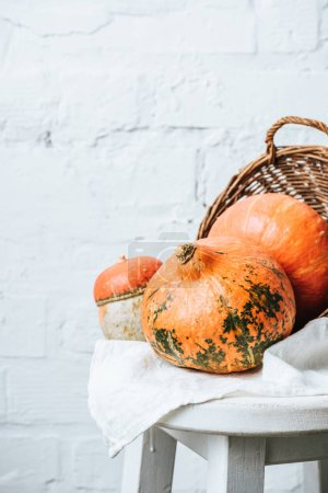 close up view of pumpkins and basket on chair with linen on white brick wall background