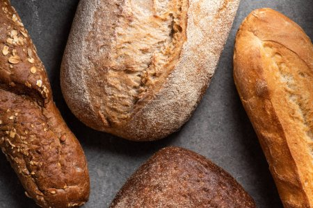 Photo for Flat lay with loafs of baked bread on grey tabletop - Royalty Free Image