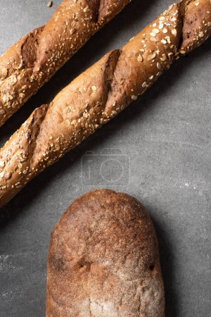 Photo for Top view of baguettes and loaf of bread on grey surface - Royalty Free Image